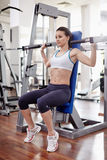 Woman at shoulder press. Young woman working in a gym at shoulder press machine Stock Photo