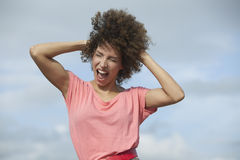Woman shouting with hand in hair Stock Images