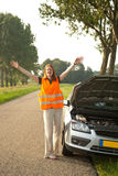 Woman shouting for help. A young female driver having car troubles on the road. Shouting for help a at oncoming traffic Stock Image