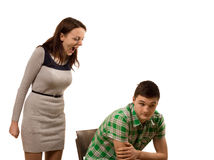 Woman shouting at her boyfriend. Attractive young women standing shouting at her boyfriend as he sits in a chair with a resigned expression,isolated on white Royalty Free Stock Photography