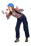 Woman shouting into a loudspeaker. Angry woman shouting into a loudspeaker Royalty Free Stock Photos