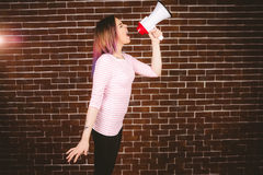 Woman shouting on megaphone. Against brick wall Royalty Free Stock Photos
