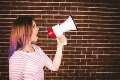 Woman shouting on megaphone. Against brick wall Royalty Free Stock Photography