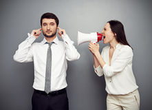 Woman shouting in megaphone at the calm man. Emotional women shouting in megaphone at the calm man Royalty Free Stock Images