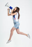 Woman shouting in megaphone. Full length portrait of a young woman shouting in megaphone isolated on a white background Royalty Free Stock Image
