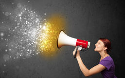 Woman shouting into megaphone and glowing energy particles explo Royalty Free Stock Photography