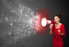 Woman shouting into megaphone and glowing energy particles explo Royalty Free Stock Photos