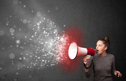 Woman shouting into megaphone and glowing energy particles explo Royalty Free Stock Image