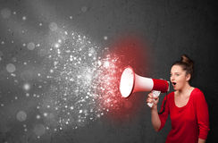Woman shouting into megaphone and glowing energy particles explode. Concept royalty free stock photo