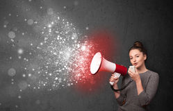 Woman shouting into megaphone and glowing energy particles explo Stock Photography