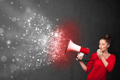 Woman shouting into megaphone and glowing energy particles explo Stock Image