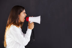 Woman shouting at the megaphone. Next to a chalkboard Stock Photography