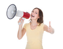 Woman Shouting Through Megaphone. Portrait Of A Young Woman Shouting Through Megaphone Over White Background Royalty Free Stock Image