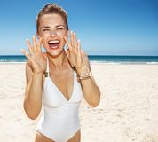 Woman shouting through megaphone shaped hands at sandy beach Stock Photos