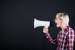 Woman Shouting Into Megaphone. Side view of a young blond woman shouting into the megaphone against black background Stock Photo