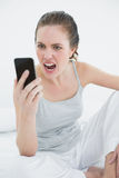 Woman shouting into mobile phone in bed Stock Photos