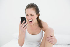 Woman shouting into mobile phone in bed Stock Photo
