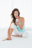 Woman shouting into mobile phone in bed Royalty Free Stock Photos