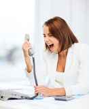 Woman shouting into phone in office Royalty Free Stock Image