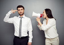 Woman shouting at the tired man. Angry women shouting at the tired men over dark background Royalty Free Stock Photography