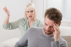 Woman Shouting To The Frustrated Man. Unhappy Woman Sitting On Sofa Shouting To The Frustrated Man Stock Image