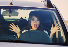 Woman shouts driving the car. Scared woman shouts driving the car stock photography