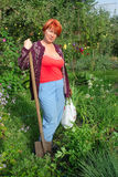 Woman with shovel in garden. Woman with shovel working and looking araond in garden Royalty Free Stock Photography