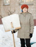Woman with shovel in snowy street Stock Photos