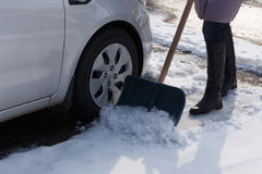 Woman shoveling here parking lot after a winter snowstorm Stock Photography