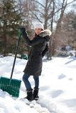Woman shoveling sidewalk Royalty Free Stock Images