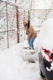 Woman shoveling snow around car Stock Image