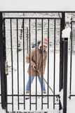 Woman shoveling snow by fence Royalty Free Stock Images