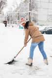 Woman shoveling snow in parking Stock Image