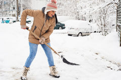Woman shoveling snow in parking Royalty Free Stock Image