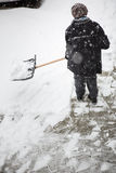 Woman shoveling snow from the sidewalk in front of his house Stock Photography