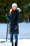 Woman shoveling too much snow. An attractive young woman holding a shovel solemnly gazes at all of the snow she has to shovel Royalty Free Stock Image