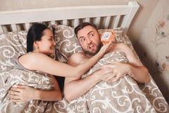 Woman show alarm clock to her husband. Royalty Free Stock Photos