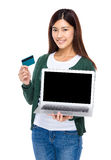 Woman show with blank screen of laptop computer and credit card Stock Images