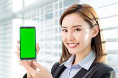 Woman show green screen of mobile. Asian businesswoman show green screen of mobile confidently in the office stock image