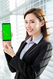 Woman show green screen of mobile. Asian businesswoman show green screen of mobile confidently in the office royalty free stock image