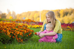 Woman show orange flowers on bed to cute baby Stock Photo
