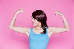 Woman show strong arm. To you on the pink background Stock Photography