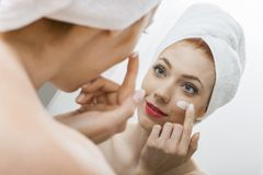 Woman After Shower Applying Cream on her Face Royalty Free Stock Image