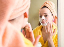 Woman after shower in bathroom mirror. Reflection of a woman applying face scrub to her face in a mirror in a bathroom stock photos
