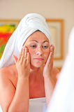 Woman after shower gets cream on face Royalty Free Stock Image