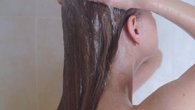 Woman in shower washing hair, slow motion video stock footage