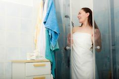 Woman showering in shower cabin cubicle. Girl showering in shower cabin cubicle enclosure. Young woman with white towel taking care of hygiene in bathroom Stock Photo