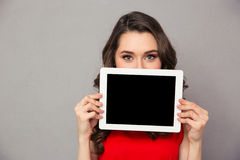 Woman showig blank tablet computer screen. Portrait of a beautiful woman in red dress showig blank tablet computer screen over gray background Stock Photo