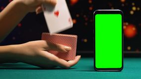 Woman showing ace of hearts near green screen smartphone, online poker app. Stock footage stock video footage