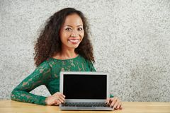 Woman showing ad on laptop. Portrait of pretty smiling girl sitting at desk and showing blank screen of her laptop royalty free stock photo